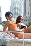 Beautiful women in bikini by pool Stock Images