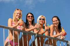 Beautiful women in bikinis smiling with drinks Royalty Free Stock Photography