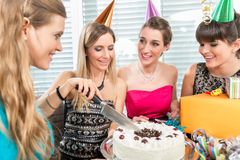 Woman blowing out candles on her birthday cake while celebrating. Beautiful women blowing out candles on her white birthday cake after making a wish while stock image