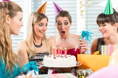 Woman blowing out candles on her birthday cake while celebrating. Beautiful women blowing out candles on her white birthday cake after making a wish while stock photo