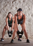 Beautiful Women in Boot Camp Style Workout. Pretty Caucasian women lift kettle bell weights with both hands Stock Photography