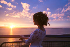 Beautiful women bride in a wedding dress with fluttering hair. Girl looking to colorful sunset on river. Beautiful woman bride in a wedding dress with fluttering Royalty Free Stock Image
