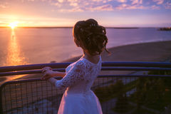 Beautiful women bride in a wedding dress with fluttering hair. Girl looking to colorful sunset on river Stock Photography