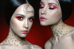 Beautiful women with bright red makeup. Fashion studio portrait of two beautiful woman with bright red makeup. Fashion and Beauty. Perfect makeup Royalty Free Stock Image