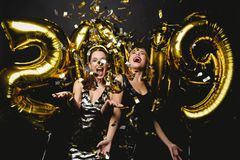 Beautiful Women Celebrating New Year. Happy Gorgeous Girls In Stylish Party Dresses Holding Gold 2019 Balloons stock image
