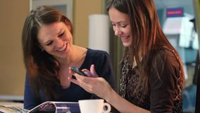 Beautiful women chat in cafe, smiling ladies watch photos phone. Stock footage stock video footage