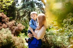 Beautiful woman with child outdoors in summer, mother and son royalty free stock image