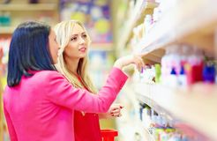 Beautiful women choose personal care product in supermarket royalty free stock images