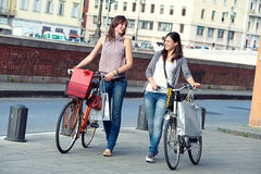 Beautiful Women in the City with Bicycles and Bags Stock Photography