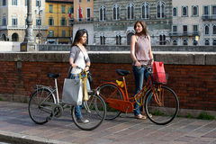 Beautiful Women in the City with Bicycles and Bags Royalty Free Stock Photo