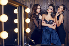 Beautiful women with dark hair in luxurious dresses posing at studio. Fashion studio photo of beautiful sensual women with dark hair in luxurious dresses with stock image
