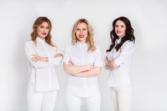 Beautiful women doctors in uniform at studio. Young professionals. Female doctors of three posing on white isolated studio background, copy space Royalty Free Stock Photos