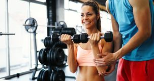Beautiful woman doing exercises in gym with personal trainer. Beautiful women doing exercises for shoulders in gym with personal trainer Stock Image