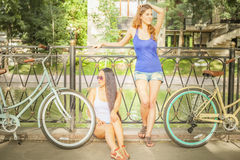 Beautiful women dressed in shorts resting after travel by bicycle Stock Image