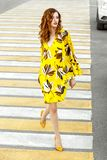 Beautiful women dressed in a stylish summer yellow with brown flowers dress is walking in a city street on a warm day stock photos
