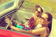 Beautiful women driving a red car retro vintage wearing accesoriess Stock Photos