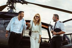 Loving couple traveling by their helicopter. Beautiful women escorted by her boyfriend out off a private helicopter with pilot standing by. Smiling couple stock photography