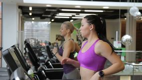 Beautiful women are exercising on treadmill in modern sports club. Two females running on aerobic simulator and talking with friendly smiles indoors. Brunette stock video footage