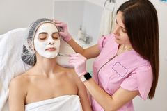 Beautiful woman with facial mask lying with closed eyes on couh at beauty salon. Cosmetologist wears pink medical gown and latex stock photography