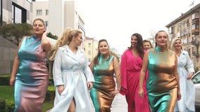 Beautiful women in fashion dresses defile on the street. Plus size Fashion Week. Slow motion. Charming girls in beautiful dresses defile on the street. Plus stock video