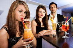 Beautiful women with friends at the bar. Drinking tequila sunrise Stock Photo