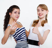 Beautiful women friends happy. Portrait of happy young friends showing thumbs up sign Stock Photo