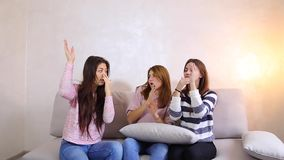 Great girls listen to music and dance, smiles on their faces and sitting on sofa background of light wall in room. stock video