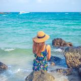 Beautiful women with hat looking to the ocean in Thailand stock photo