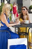 Beautiful Women Having Coffee With Shopping Bags. Two beautiful and sophisticated young women friends wearing sunglasses and having coffee around a modern city Stock Images