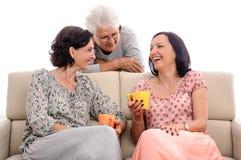 Beautiful women having fun at home senior lady listening Royalty Free Stock Photo