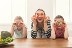 Beautiful woman with her daughters cooking salad and having fun. Beautiful women with her daughters looks happy while cooking salad anf having fun in the kitchen Stock Image