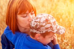 Beautiful woman and her little son. Beautiful women and her little son trembling and strongly embracing, on field background. Summer portrait of mother and son royalty free stock photos