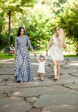 Beautiful women holding baby girl by hands and walking at park Stock Images