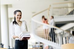 Beautiful woman holding books in a library royalty free stock photography