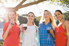 Beautiful women holding a glasses of red wine in park royalty free stock images