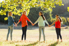 Beautiful women holding hands in park royalty free stock images