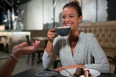 Beautiful woman interacting while having coffee. Beautiful women interacting while having coffee in restaurant Royalty Free Stock Images