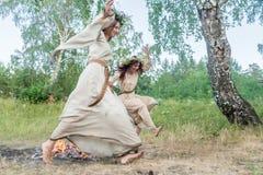 Beautiful women jumping through fire Stock Photography