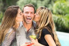 Beautiful women kissing happy man. Close-up of beautiful women kissing happy men during party Royalty Free Stock Image