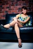 Beautiful women on leather sofa Stock Photos