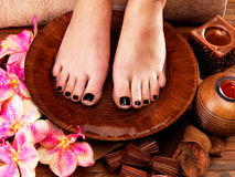 Beautiful women legs with black pedicure. After Spa procedures - Spa treatment concept Royalty Free Stock Photography