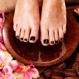 Beautiful women legs with black pedicure after Spa procedures. Spa treatment concept Royalty Free Stock Images