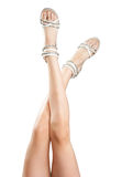 Beautiful women legs in sandals up in the air. Isolated on the white background Royalty Free Stock Photography