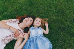 Beautiful woman in light dress and little cute child baby girl lie on green grass lawn in park and looking up. Mother. Beautiful women in light dress and little royalty free stock image