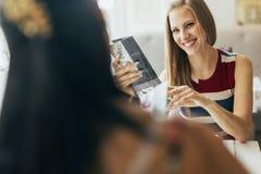 Beautiful women looking at menu in restaurant Stock Photos