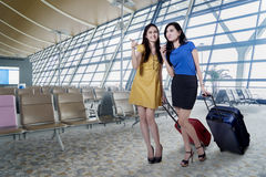 Beautiful women with luggage in airport Stock Photography