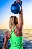 Beautiful women man group are doing sport fitness cross at the lake with a kettlebell. Young beautiful sport woman is doing her cross workout at the water to get stock photography