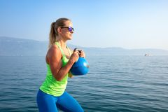 Beautiful women man group are doing sport fitness cross at the lake with a kettlebell. Young beautiful sport woman is doing her cross workout at the water to get royalty free stock photography