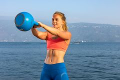 Beautiful women man group are doing sport fitness cross at the lake with a kettlebell. Young beautiful sport woman is doing her cross workout at the water to get stock photos