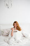 Beautiful women with morning coffee or tea in bed Stock Photography